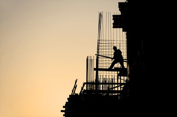 Construction worker silhouette at sunset