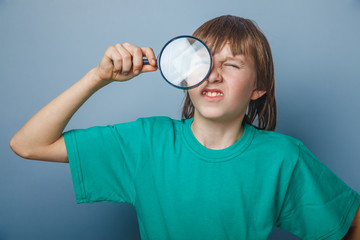 European-looking boy of ten years holding a magnifying glass, a