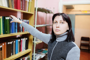 Woman in the library takes the book from the shelf