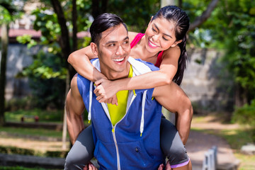 Asian man carrying his girlfriend piggyback for sport