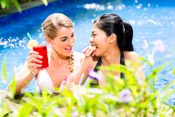 Women in Asian hotel pool drinking cocktails