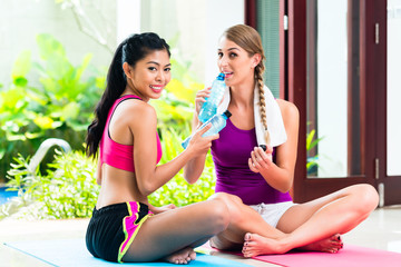 Women friends relaxing after fitness exercise