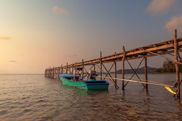 Sunset over the beautiful tropical beach with bridge and boat