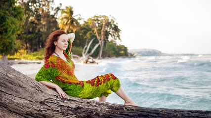 Beautiful woman in indian bright dress is sitting on the snag on