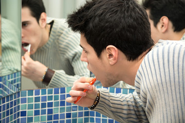 Headshot of attractive young man brushing teeth