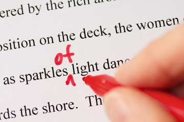 Hand with Red Pen Proofreading Text Closeup