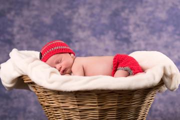 Newborn baby sleeping in a basket with purple background.