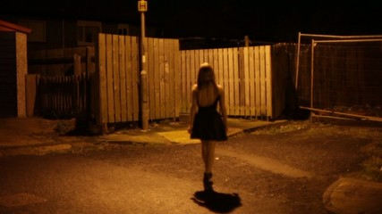 youngwoman walks down dark street alone