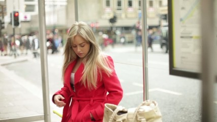 young woman listens to music at bus stop