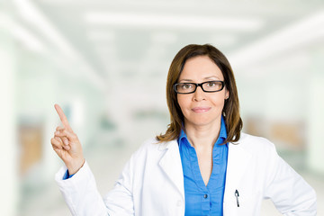 Confident female doctor with glasses pointing away with finger
