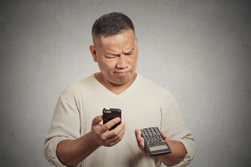 Confused man looking at his smart phone holding calculator
