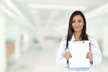 Happy doctor holding clipboard standing in hospital hallway