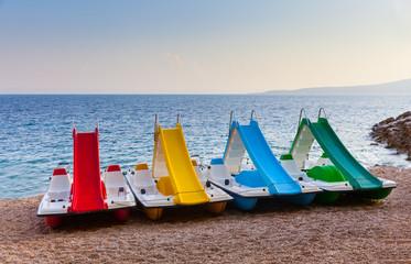 Four colored catamarans on the beach