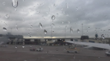 Airport transport view through wet moving aircraft window
