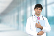 Smiling male doctor with clipboard standing in hospital hallway - 80430815