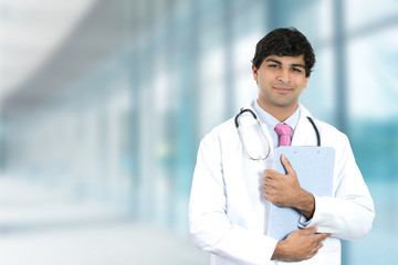 Smiling male doctor with clipboard standing in hospital hallway