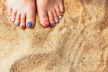 female sea style pedicured feet on summer shore sand on sunny da
