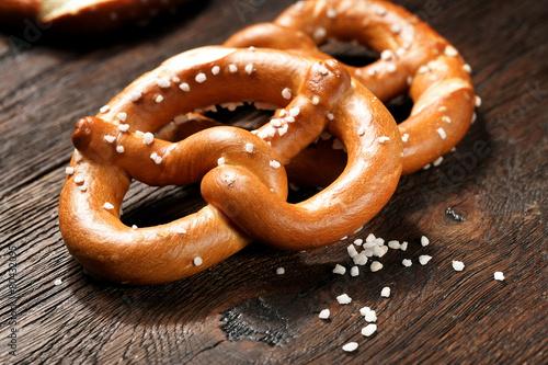 Aluminium Bakkerij Fresh pretzels with sea salt close-up on dark board background
