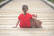 Little girl in a red dress waiting on a boardwalk hugging teddyb - 80433054