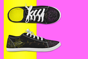Sneakers with floral pattern in bright multi-colored background.