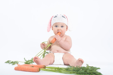 Chubby baby in rabbit hat with mouth and eyes wide open biting f