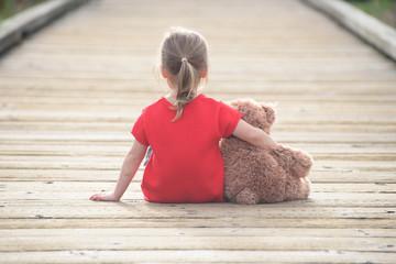 Little girl in a red dress waiting on a boardwalk hugging teddyb