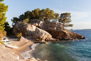 Coast of Croatia. Rocks, boats and pine trees.