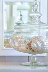 Sea shells displayed in glass jar. Beach cottage interior