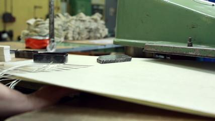 Worker cuts parts using semi-automatic machine