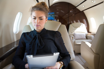 woman in corporate jet looging at tablet computer