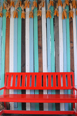 Red bench in front on wooden wall