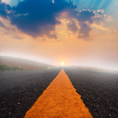 Long road and sunset with sun rays.