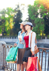 Two beautiful girls with shopping bags and cup of coffee in the