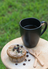 blueberry muffin with coffee cup on green background
