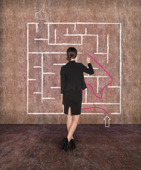 Businesswoman drawing labyrinth on wall