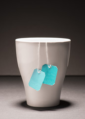 Teacup filled with strong hot tea and two teabags