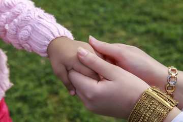 Adult woman hold little girl hand in green garden