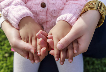 Adult woman hold little girl hands in green garden