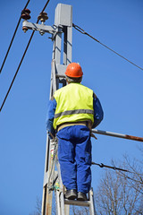 Electrician is working next to an electricity pylon