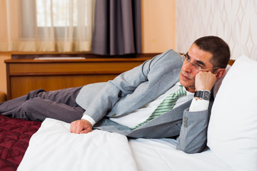 Tired businessman is lying on bed and thinking