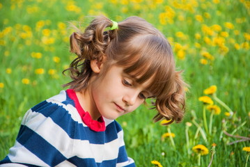 thoughtful little girl on  background lawn with dandelions