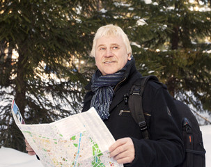 an elderly man with a map and a backpack in the winter