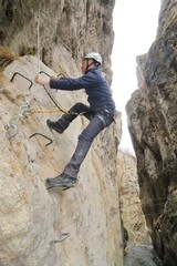 A hiker on the via ferrata of Chianocco ( Italy )