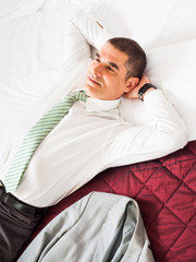 Businessman is resting on a bed and thinking