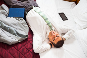 Tired businessman is sleeping on bed