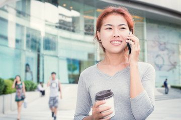 beautiful young women call phone and hold coffee cup urban backg