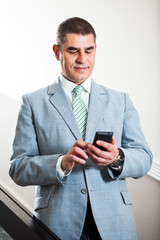 Businessman typing sms message
