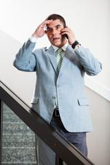 Businessman talking on the phone hearing bad news