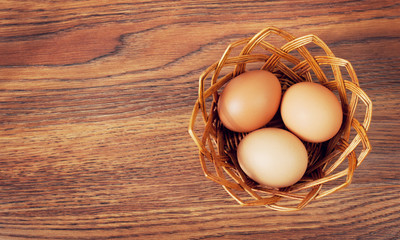 Eggs in a basket on wooden table