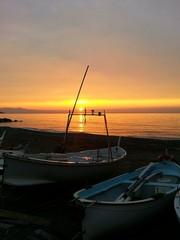 Alba in riva al mare con le barche dei pescatori